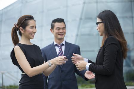 Aziatische Onderneemster presenteert haar visite kaartje naar een vrouwelijke collega. Stockfoto - 54492175