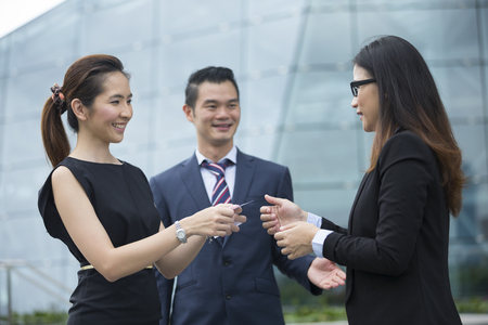 gente saludando: Empresaria asiática presentar su tarjeta de visita a un colega de negocios femenina.