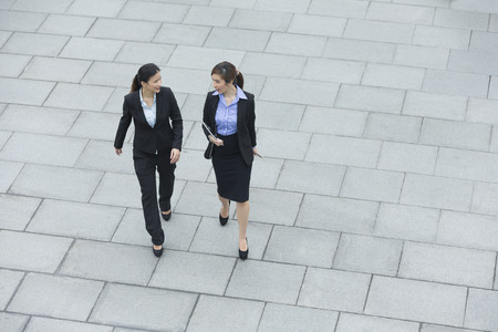 angle: Elevated view of two Chinese business women walking outside modern office building.