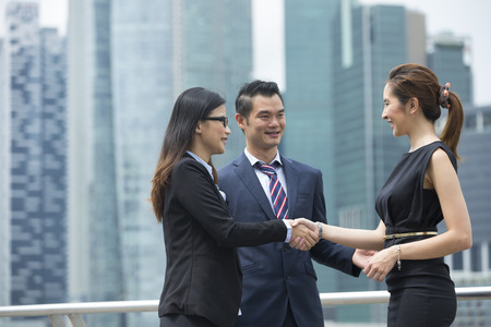 business in hand: Chinese business women shaking hands outside the office. Business concept. Stock Photo