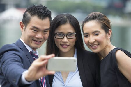 Happy group of Asian business people using a smart phone to take selfie self-portrait photograph. Stock Photo