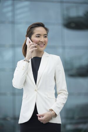 Portrait of a Chinese businesswoman standing outside talking on her smart phone. 版權商用圖片