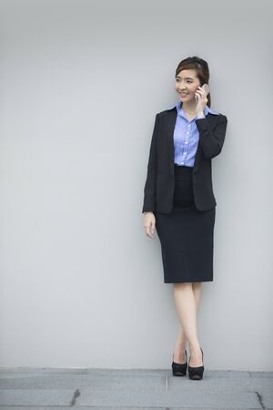asian businesswoman: Portrait of a Chinese businesswoman standing leaning against a grey wall using smart mobile phone.