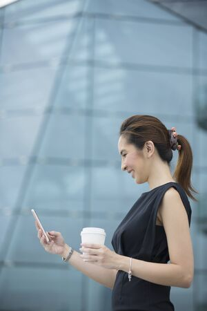 phone message: Portrait of a Chinese businesswoman standing outside using her smart phone to send a message.