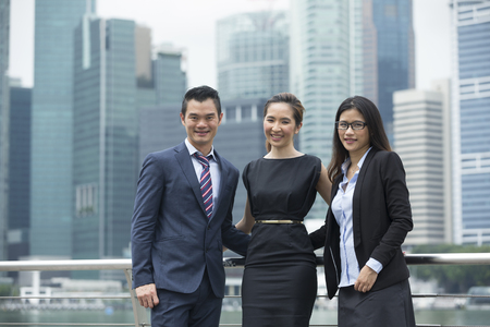 management team: Portrait of three Chinese business colleagues in a modern urban setting. Stock Photo