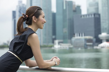 away: Cheerful Chinese business woman standing outside with office buildings in the background. Portrait of an Asian business woman looking away. Stock Photo