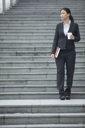 looking away from camera: Successful Asian businesswoman standing on steps looking away from camera. Stock Photo