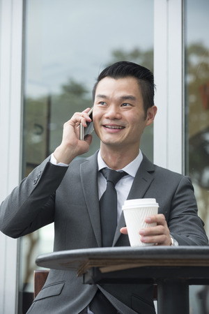 chinese businessman: Portrait of a Chinese businessman using a smart phone in a cafe. Stock Photo