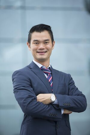 smiling businessman: Portrait of a Chinese businessman outside modern office building. Asian businessman smiling & looking at the camera with blurred office buildings as a background. Stock Photo