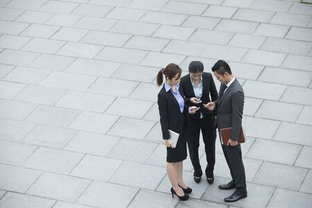 associates: Group of Chinese business colleagues using mobile phones outside the office.