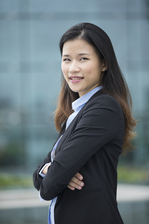 mujer alegre: Cheerful Chinese business woman standing outside with office buildings in the background. Portrait of an Asian business woman looking at the camera.