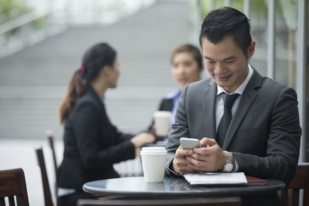 Portrait of a Chinese businessman using a smart phone in a cafe. Stock Photo