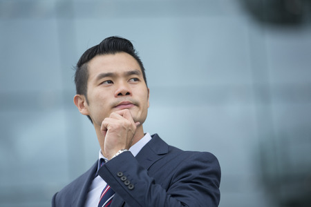 chinese businessman: Portrait of a Chinese businessman outside modern office building, looking away. Stock Photo