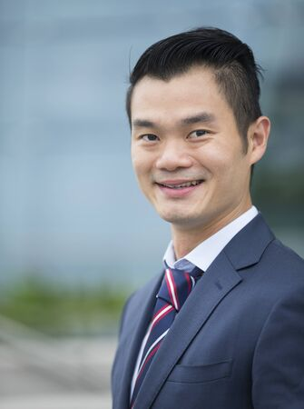 chinese businessman: Happy Chinese businessman outside modern office building, looking at the camera. Stock Photo