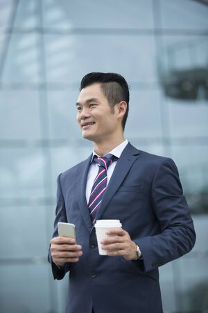 looking away from camera: Portrait of a confident Chinese Business man standing in modern city. Business man looking away from camera.