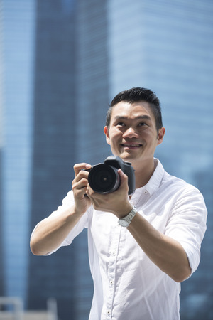 outside shooting: Portrait of happy Chinese man taking photos with a camera in the city. Asian Photographer shooting outside with digital camera.