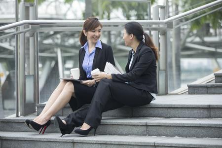 modern office: Portrait of two Asian business women talking outside modern office building. Chinese business colleague talking outside.