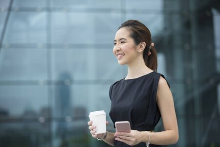 asian businesswoman: Portrait of a Chinese businesswoman standing outside holding her smart phone. Asian business woman looking away. Stock Photo