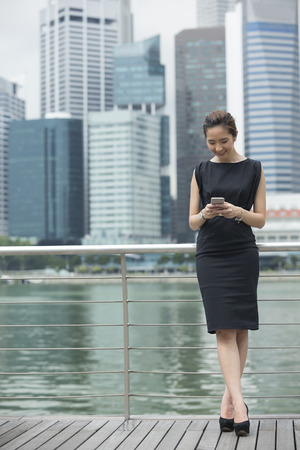 asian businesswoman: Portrait of a Chinese businesswoman standing outside using her smart phone to send a message.