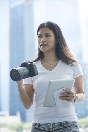 mapa de china: Retrato de turismo asiático feliz que sostiene una cámara, el mapa y la tableta digital. Hermosa mujer china el día de fiesta perfecto. Foto de archivo