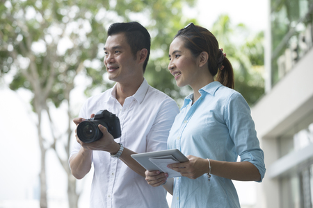 mapa de china: Feliz pareja china turismo con un mapa, c�mara y la tableta en la ciudad. Foto de archivo