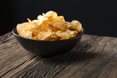 heap up: Potato chips in a bowl. A heap of potato crisps piled up in a bowl. The food is sitting on a rustic wooden background.