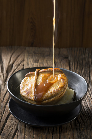 pie: Traditional British meat pie with mashed potatoes. Hot gravy is being poured on the pie. The food is sitting on a rustic wooden background. Stock Photo