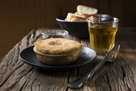 uk cuisine: A freshly cooked meat pie on the wooden table. Traditional and wholesome food sitting on a rustic wooden table.