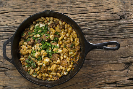hearty: Hearty bean and sausage stew sitting on a rustic wooden table. Stock Photo