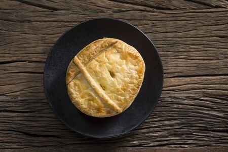 meat pie: A Traditional British meat pie sitting on a rustic wooden table.