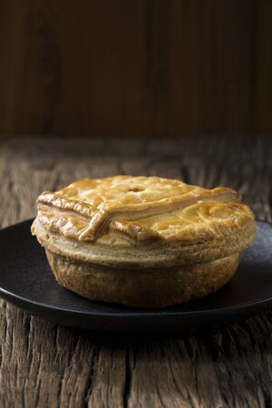 A Traditional British meat pie sitting on a rustic wooden table.