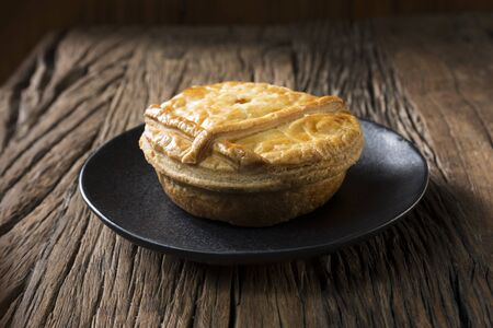 uk cuisine: A Traditional British meat pie sitting on a rustic wooden table.