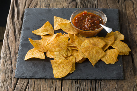 heap up: Above view of Nacho tortilla chips spread out on a slate board. A heap of tortilla crisps piled up in a board. The food is sitting on a rustic wooden background. Stock Photo