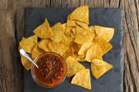 nachos: Above view of Nacho tortilla chips spread out on a slate board. A heap of tortilla crisps piled up in a board. The food is sitting on a rustic wooden background. Stock Photo