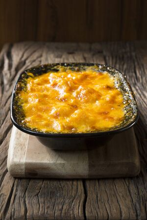 uk cuisine: Homemade Macaroni and Cheese on a rustic wooden table. Traditional and wholesome food sitting on a rustic wooden table. Stock Photo
