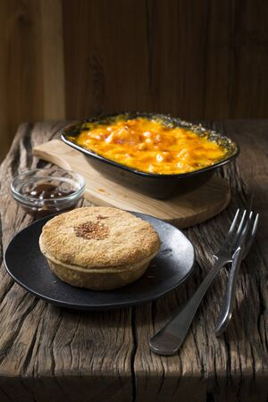 wholesome: Freshly cooked meat pie and Macaroni and Cheese on a rustic wooden table. Traditional and wholesome food sitting on a rustic wooden table. Stock Photo