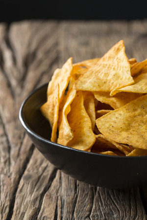 heap up: Nacho tortilla chips in a bowl. A heap of tortilla crisps piled up in a bowl. The food is sitting on a rustic wooden background. Stock Photo
