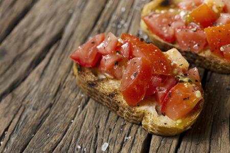 tomate: Brochettes de tomates. Tomate sur pain grillé sur une table en bois rustique.