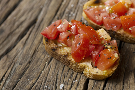 tomates: Tomato Bruschetta. Tomato on toasted bread on a rustic wooden table.