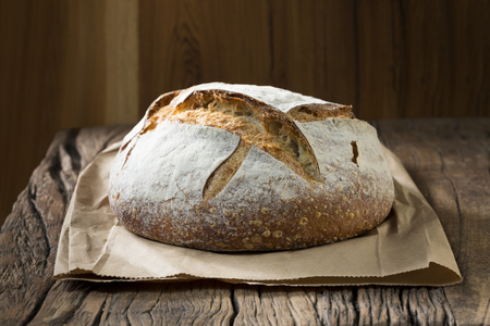 wooden plate: A freshly baked rustic, sourdough loaf of bread on an old wooden table.
