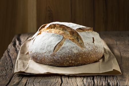 tablero: Un recién horneado del pan rústico, masa fermentada de pan en una tabla de madera.