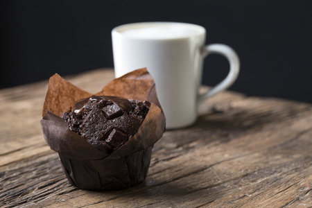A freshly baked Chocolate Muffin and a Cappuccino coffee, sitting on an old rustic, wooden table.
