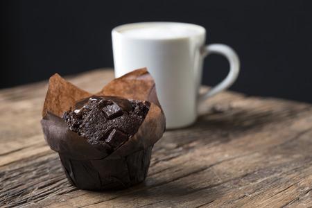 Un Muffin fraîchement cuit au chocolat et un café Cappuccino, assis sur un vieux rustique, table en bois. Banque d'images - 54597310