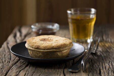 wholesome: A freshly cooked meat pie on the wooden table. Traditional and wholesome food sitting on a rustic wooden table.