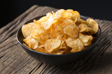 Potato chips in a bowl. A heap of potato crisps piled up in a bowl. The food is sitting on a rustic wooden background. Stock Photo