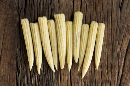wood board: A row of baby corn on a rustic wooden table.