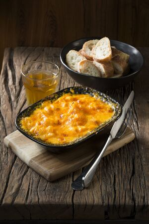 wholesome: Homemade Macaroni and Cheese on a rustic wooden table. Traditional and wholesome food sitting on a rustic wooden table. Stock Photo