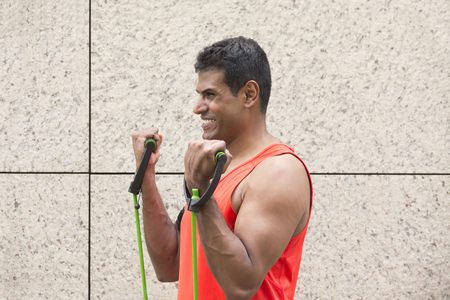 strength training: Portrait of an athletic Indian man using stretch bands outdoors in urban setting. Stock Photo