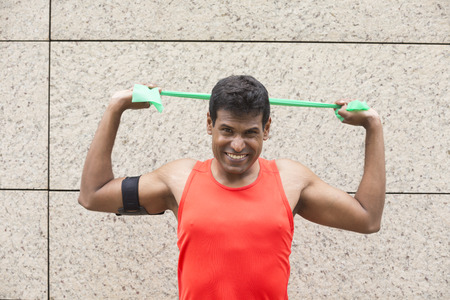elastic band: Portrait of an athletic Indian man using stretch bands outdoors in urban setting. Stock Photo