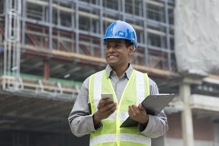 Portret van een mannelijke Indiase bouwer of industrieel ingenieur op het werk met behulp van de telefoon.